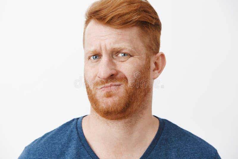 Dźwięki podejrzani i ordynarni Portret niepewna nierada śmieszna rudzielec smirking z chłodno fryzurą, marszczący brwi, i zdjęcie stock