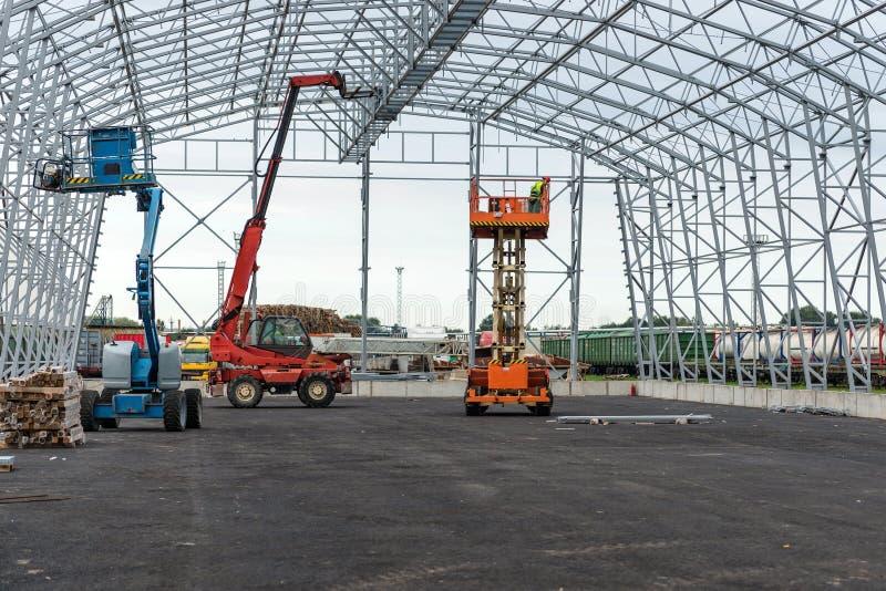 Dźwignięcie z estradową pracą w magazynowym hangar budowy polu zdjęcia royalty free