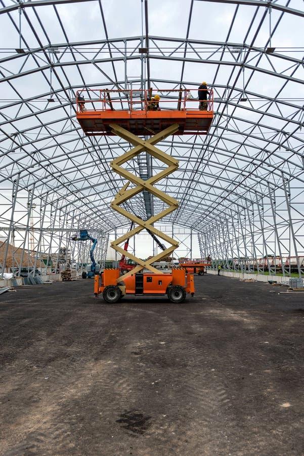 Dźwignięcie z estradową pracą w magazynowym hangar budowy polu zdjęcie royalty free
