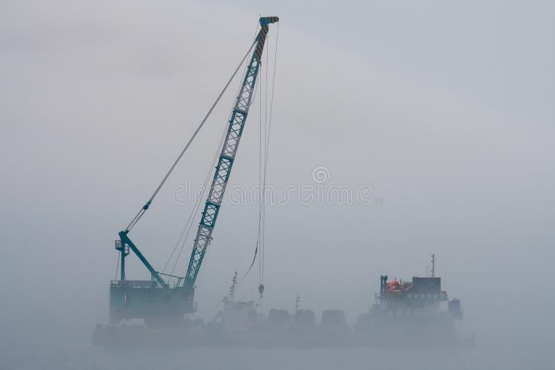Dźwigowa barka po środku ciężkiego mgła ciosu od morza zdjęcie stock