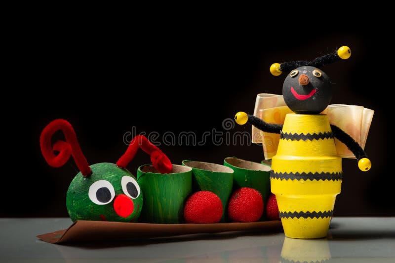 Dżdżownica robić papier toaletowy rolki i żółta pszczoła robić mali kwiatów garnki dzieckiem obrazy stock