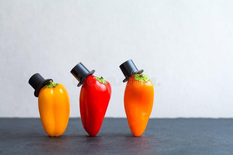 Dżentelmenów pepperes czarnych kapeluszy pojęcie Piękni staromodni czerwoni żółci pomarańczowi warzywo charaktery, czerni kamienn zdjęcie royalty free