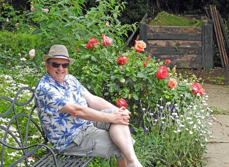 Dżentelmen w ogrodowej jest ubranym lata Panama trilby kwiatów róż siedzenia kapeluszowej ławce zdjęcia royalty free