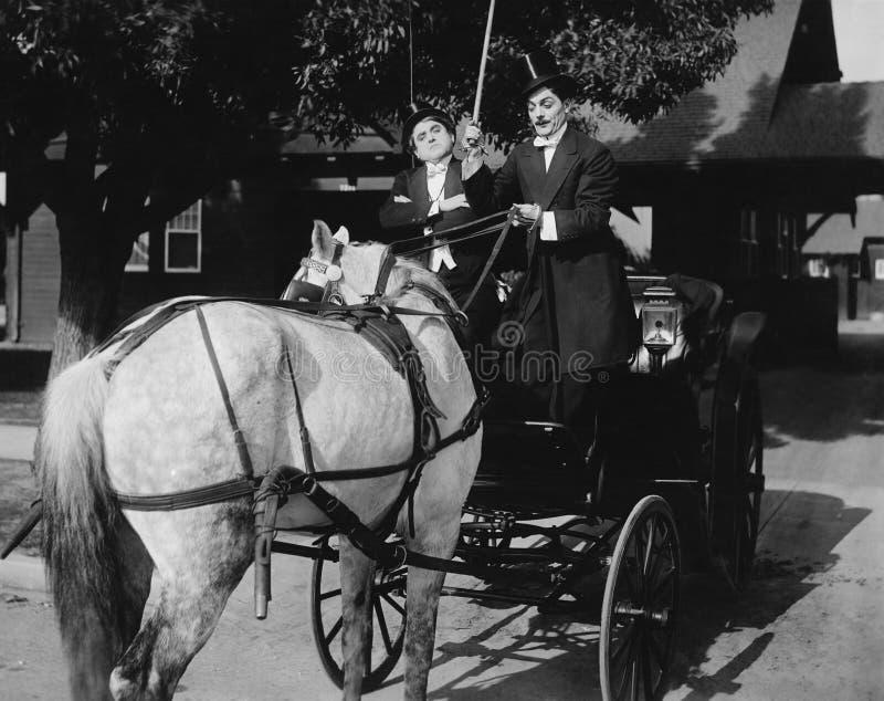 Dżentelmeny jedzie fracht z koniem uczepiającym się backwards (Wszystkie persons przedstawiający no są długiego utrzymania i żadn zdjęcie stock