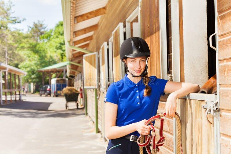 Dżokej dziewczyny pozycja jeździeckimi stajenkami z ogranicza zdjęcie stock