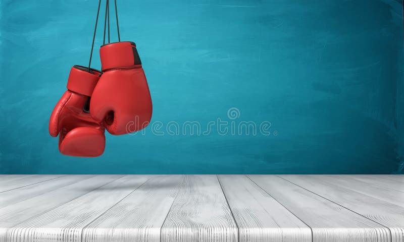 3d垂悬在蓝色黑板背景前面的一张木书桌上的两个红色拳击手套翻译  皇族释放例证