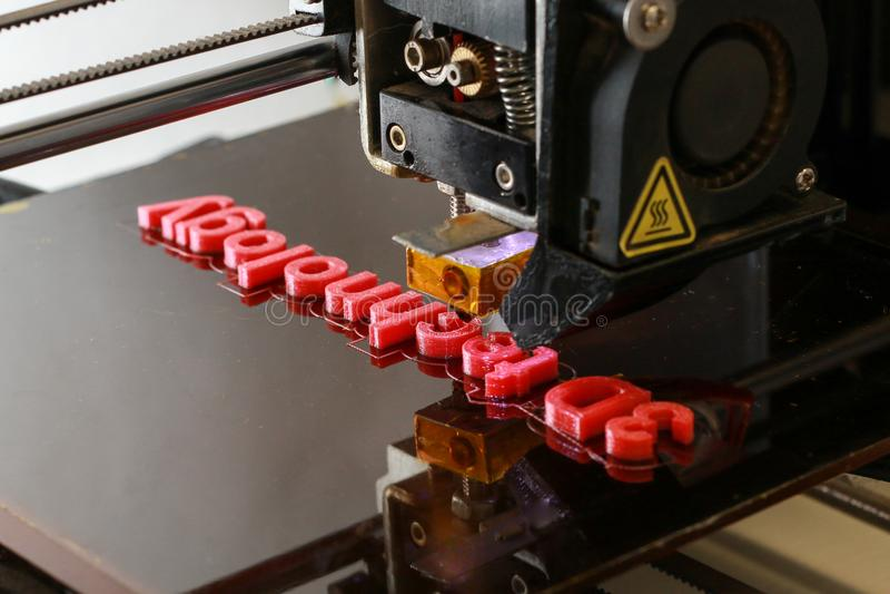 3D打印机与红色塑料的打印词 图库摄影