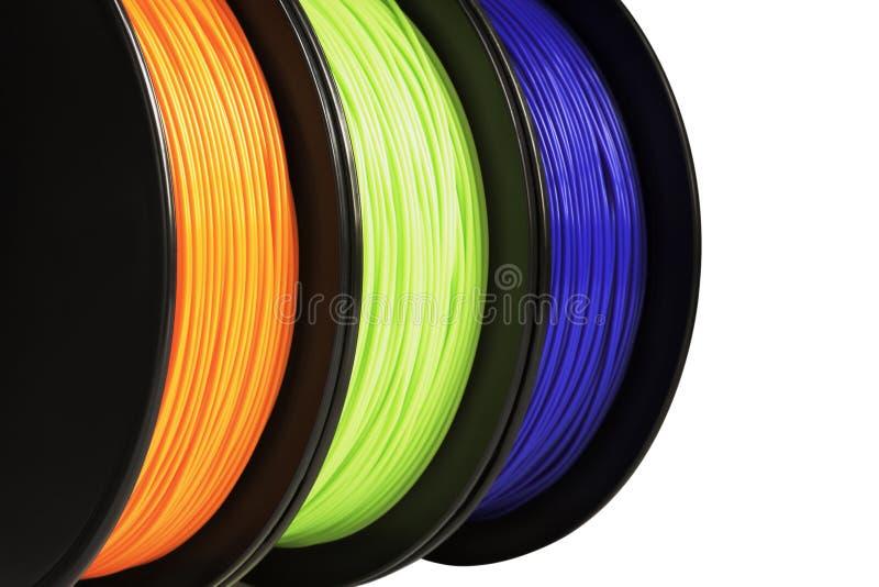 3d打印的细丝 明亮termoplastic霓虹橙色,绿色和蓝色颜色 背景查出的白色 免版税库存图片