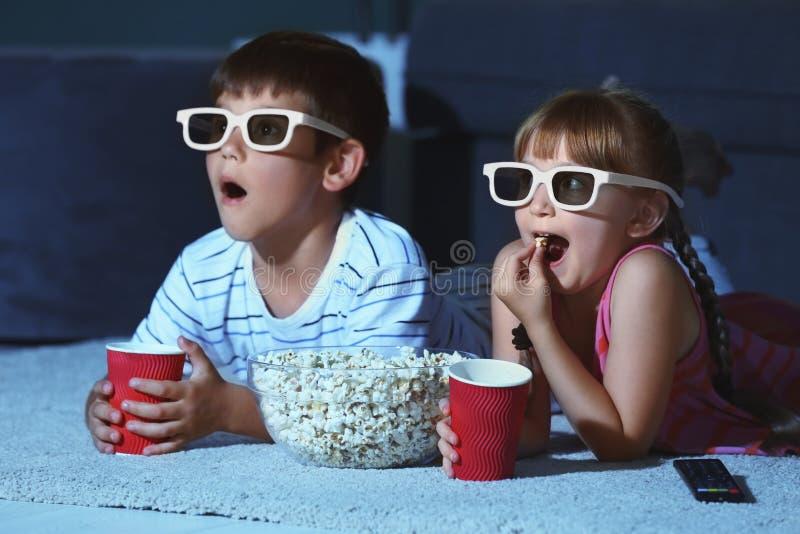 3d玻璃电影的逗人喜爱的孩子在地毯在晚上 库存照片