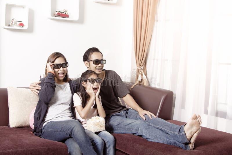 戴3D眼镜的年轻亚洲家庭看电视 免版税库存图片