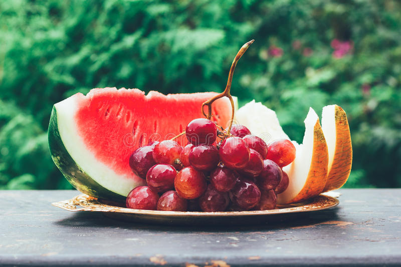 D'été de fruit de baie toujours la vie avec des tranches de groupe de pastèque, de melon et de raisin photographie stock