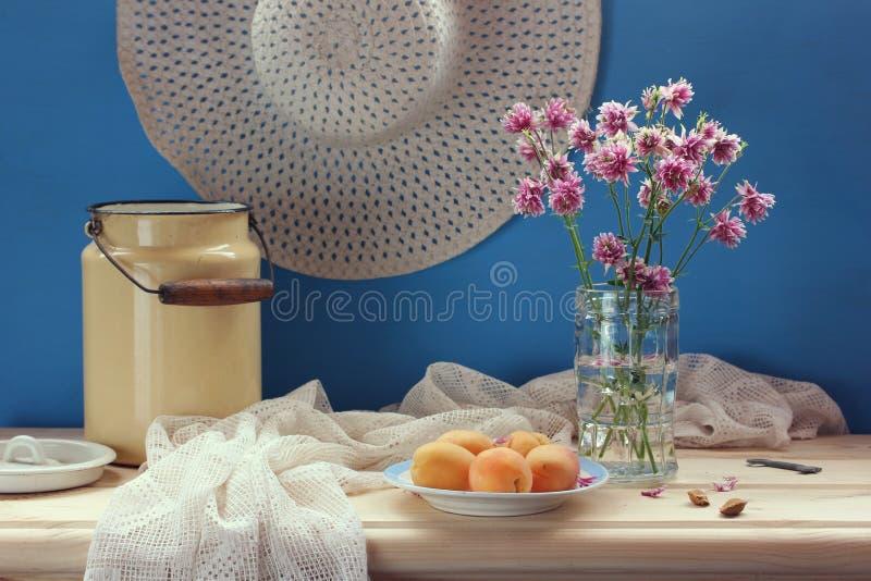 D'été toujours la vie avec les fleurs, le fruit et un chapeau en osier photo libre de droits