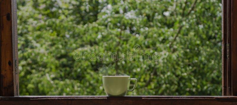 D'été toujours la vie confortable : tasse de thé chaud sur le rebord de fenêtre et la pluie de vintage dehors appartement Pluie p photo stock