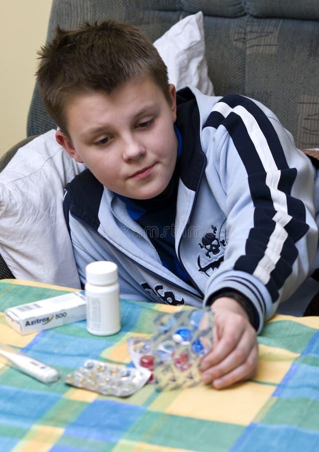 d'adolescent malade de médecines de garçon images libres de droits