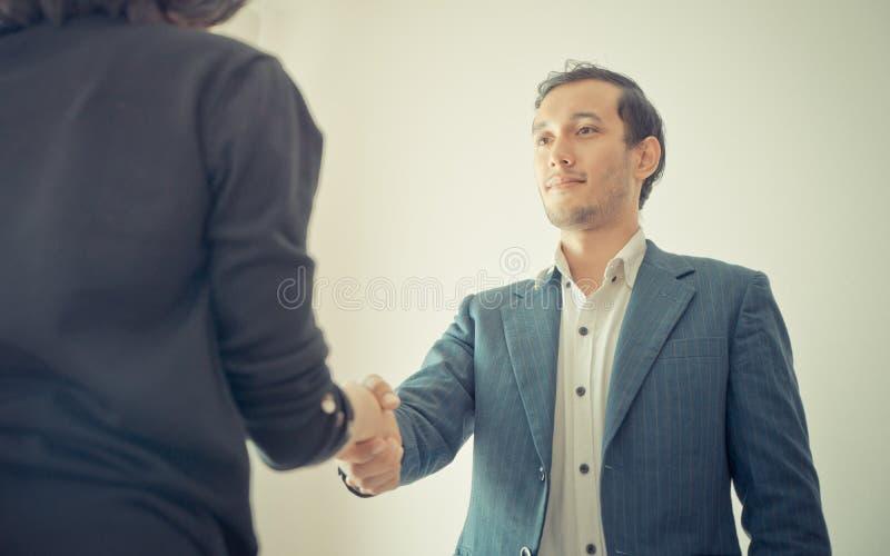 D'affaires d'homme sourire heureusement serrant la main avec l'associé photographie stock libre de droits