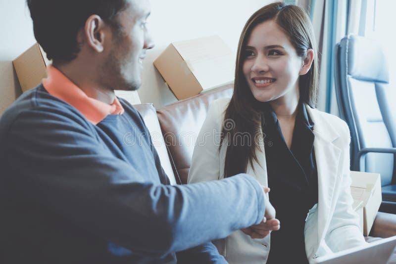 D'affaires d'homme sourire heureusement serrant la main avec l'associé féminin image libre de droits