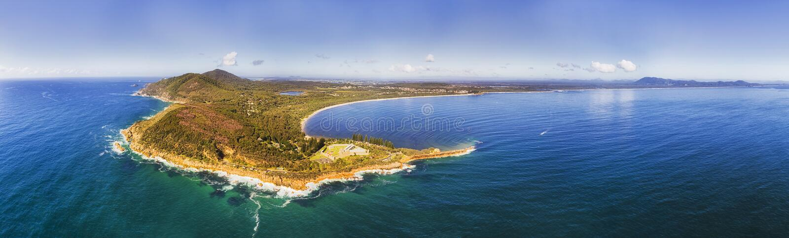 D Arakoon Gaol From Sea Pan. Trial bay gaol in Arakoon national park at the tip of small cape forming shallow bay on Pacific coast of Australia - wide panorama stock photography