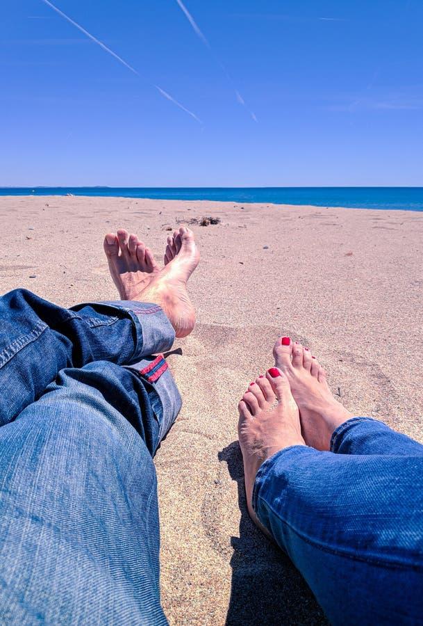 D?as de fiesta de las vacaciones Primer de los pies del hombre y de la mujer relxing en la playa en el sol de goce sunbed en d?a  imagenes de archivo