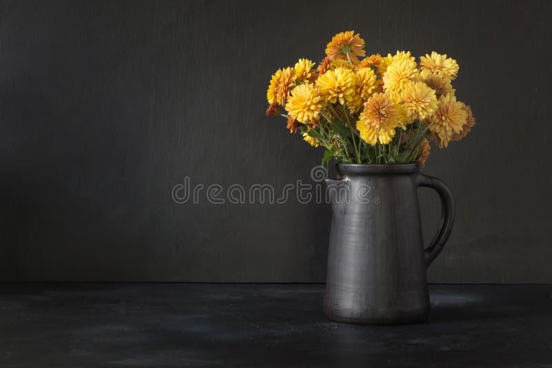 D'automne d'obscurité toujours la vie Tombez avec les fleurs jaunes de chrysanthème dans le vase à clayware sur le noir image stock