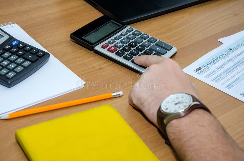 D?claration d'imp?t 1040 Une main masculine dactylographie quelque chose sur une calculatrice dans la perspective d'une table et  photographie stock libre de droits