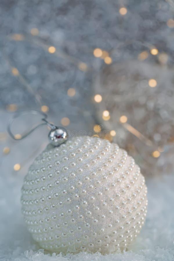 D?coration de No?l Perles blanches de nacre de boule sur une neige et un beau fond brouill? de bokeh ?clatant avec les lumi?res r images stock