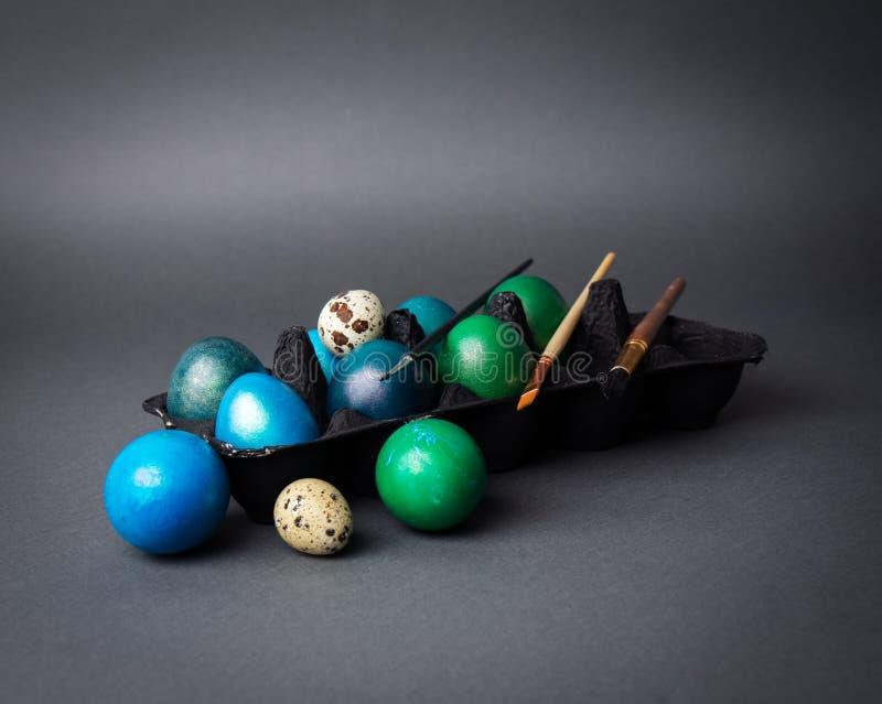 D?a de fiesta de Pascua: huevos pintados coloreados en una caja negra y un cepillo contra un fondo oscuro imágenes de archivo libres de regalías