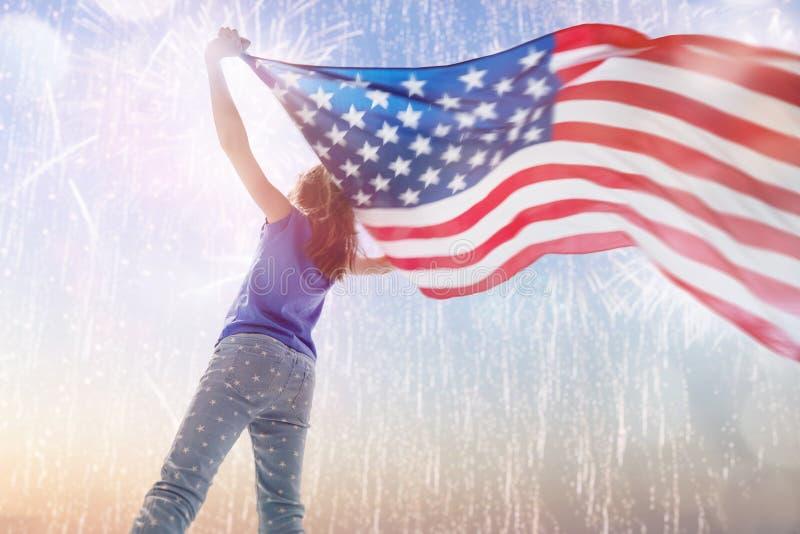 D?a de fiesta patri?tico Niño feliz con la bandera americana fotografía de archivo