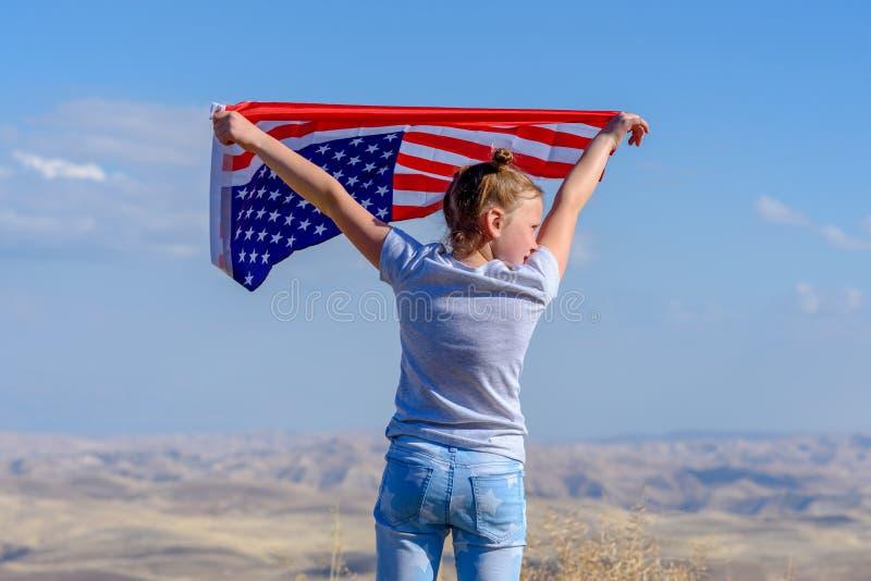 D?a de fiesta patri?tico Ni?o feliz, muchacha linda del peque?o ni?o con la bandera americana Los E.E.U.U. celebran el 4 de julio imágenes de archivo libres de regalías