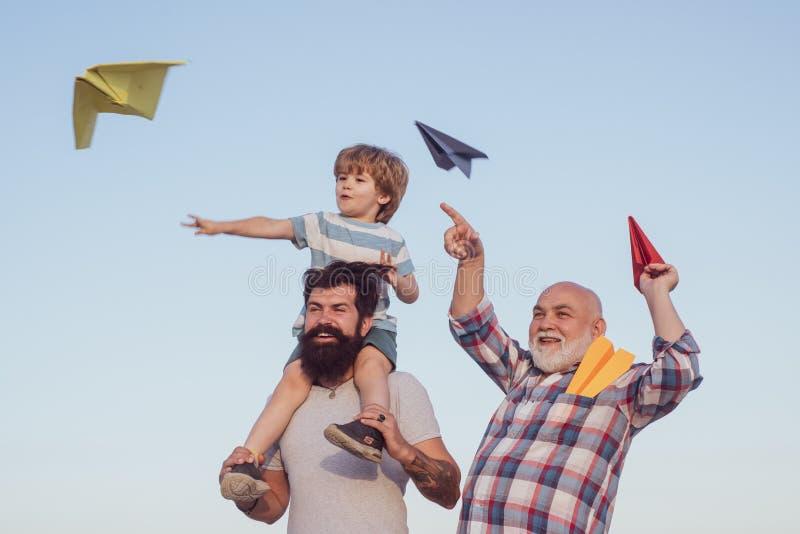 D?a de padres feliz Padre y nieto de abuelo felices con el aeroplano de papel del juguete sobre fondo del cielo azul y de las nub foto de archivo libre de regalías
