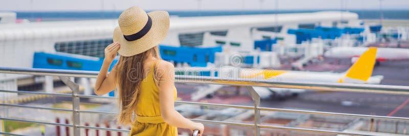 D?but de son voyage Le beau ltraveler de jeune femme dans une robe jaune et une valise jaune attend son vol image libre de droits
