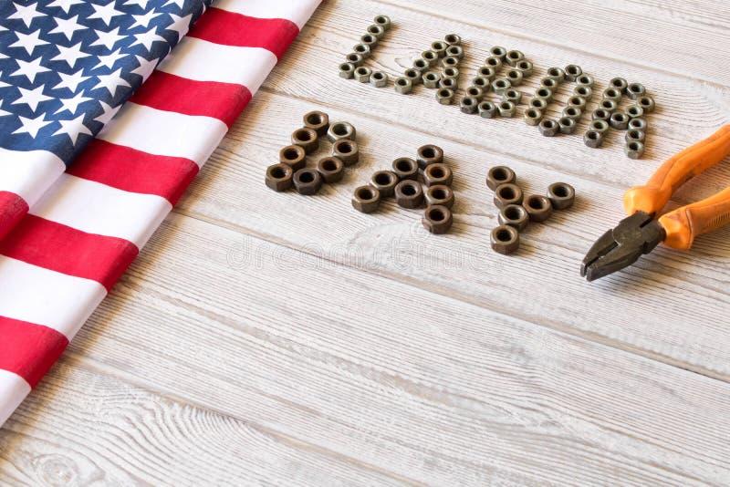 D?a del Trabajo Bandera americana y Día del Trabajo de la inscripción y diversas herramientas en un fondo de madera ligero foto de archivo