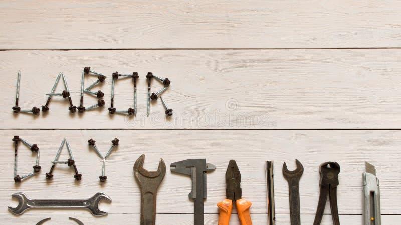 D?a del Trabajo D?a del Trabajo de la inscripci?n y diversas herramientas en un fondo de madera ligero fotografía de archivo libre de regalías