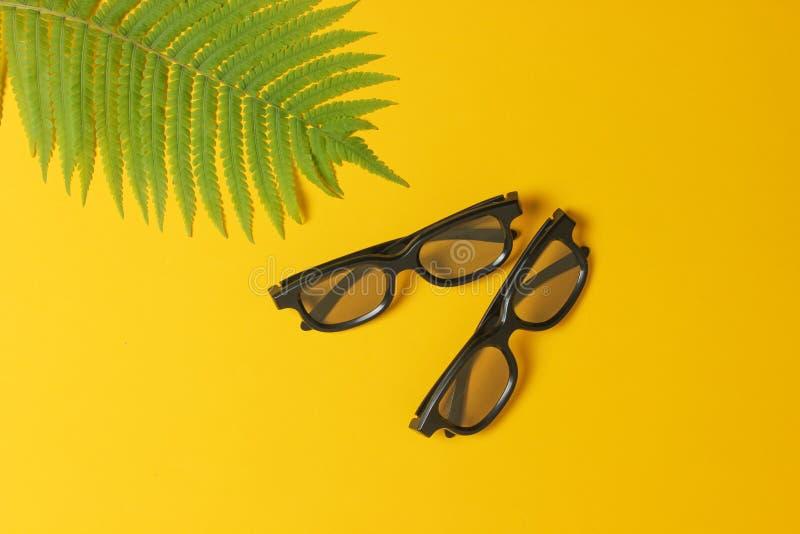 3D exponeringsglas, ormbunkeblad på en gul bakgrund Bästa sikt, minimalism royaltyfria foton