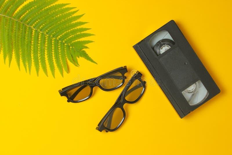 3D exponeringsglas, videokassett, ormbunkeblad på en gul bakgrund Bästa sikt, minimalism arkivfoton