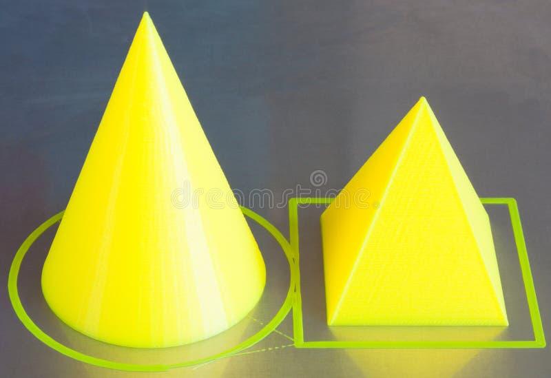 3d gedrukte cijfers van kegel en pyramide Gele 3D printerpla gloeidraad De achtergrond van het aluminiumbed Grens, die de printer stock afbeeldingen