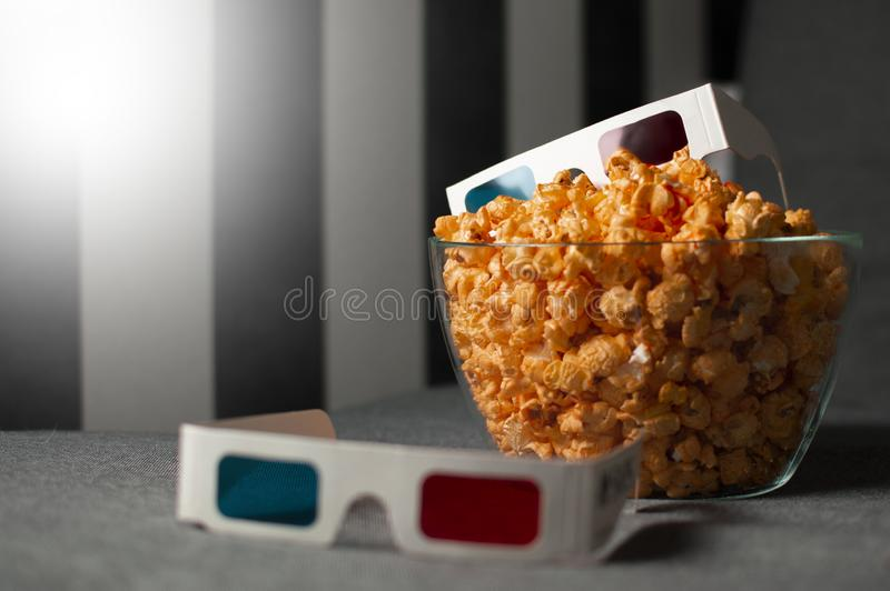 3D glasses and cheesy popcorn lie in a glass plate on a gray bed stock images