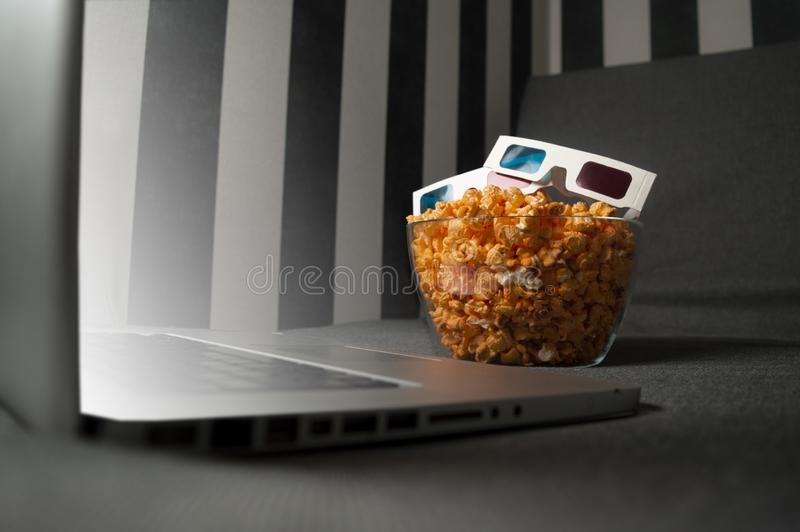 3D glasses, popcorn and a laptop are lying on the sofa in the room at night. The computer screen glows stock photography