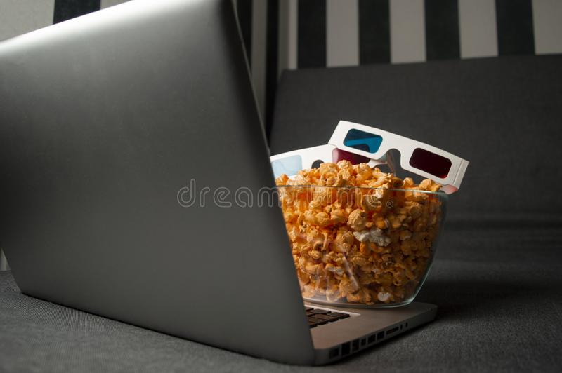 3D glasses, popcorn and a laptop are lying on the sofa in the room at night. The computer screen glows royalty free stock images