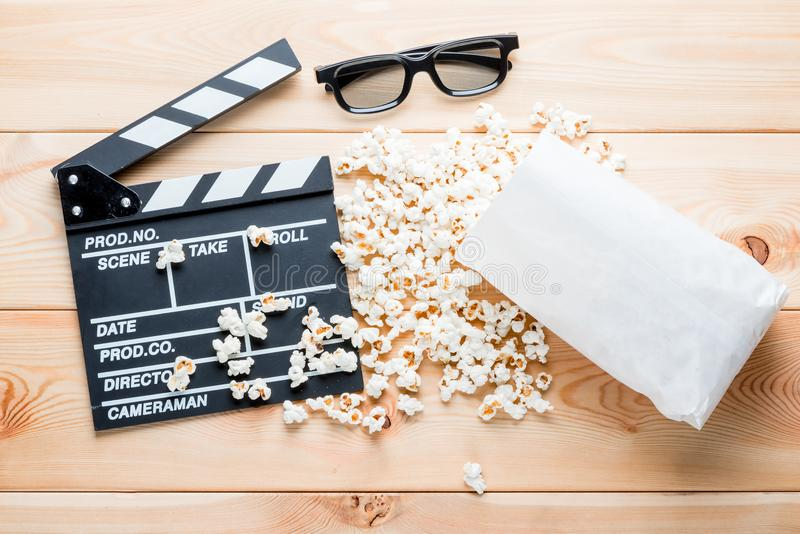 3D glasses, video clapper and delicious popcorn - objects on woo royalty free stock photography