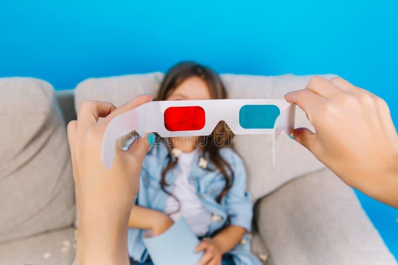 3D glazen in handen op meisje met popcornachtergrond Koelend op laag, die op film voorbereidingen treffen thuis te letten royalty-vrije stock foto's