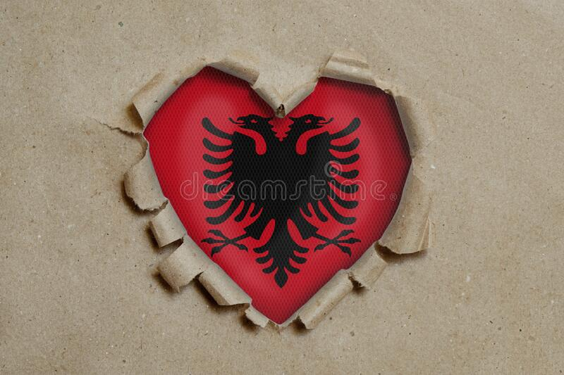 Heart shaped hole torn through paper, showing Albanian flag. 3d Image of Heart shaped hole torn through paper, showing Albanian flag royalty free stock image