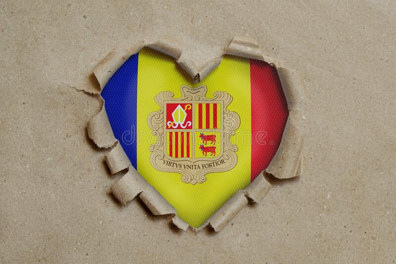 Heart shaped hole torn through paper, showing Andorran flag stock images