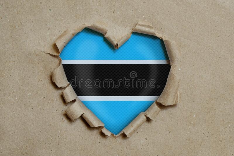 Heart shaped hole torn through paper, showing Botswana flag royalty free stock photography