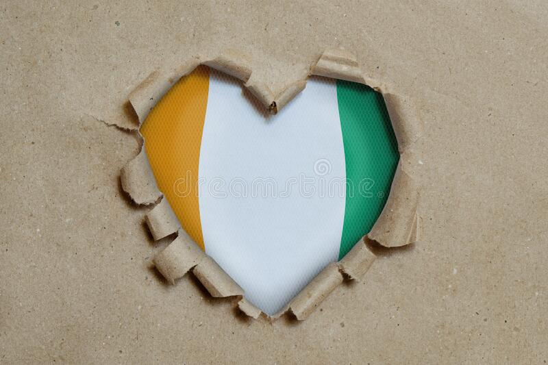 Heart shaped hole torn through paper, showing Cote d`ivoire flag royalty free stock photo