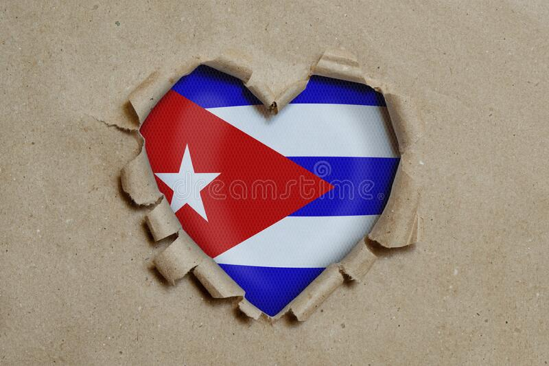 Heart shaped hole torn through paper, showing Cuban flag stock images