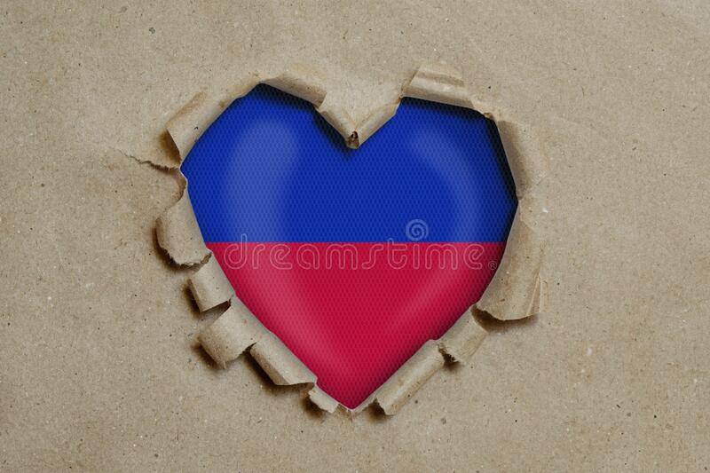 Heart shaped hole torn through paper, showing Haitian flag royalty free stock images