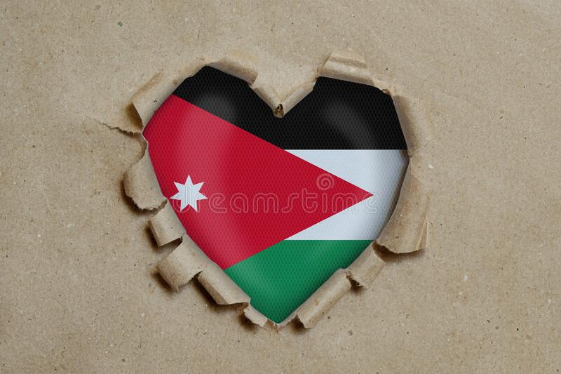 Heart shaped hole torn through paper, showing Jordan flag royalty free stock photos
