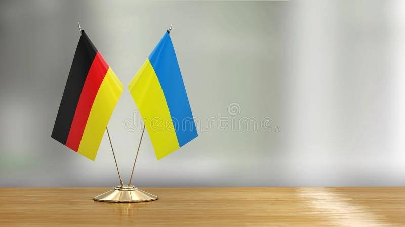Ukrainian and German flag pair on a desk over defocused background. 3d Image of Ukrainian and German flag pair on a desk over defocused background vector illustration