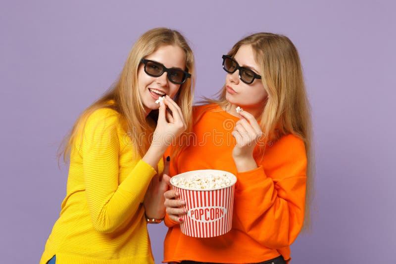 3d imax玻璃电影影片的,在柔和的淡色彩隔绝的举行玉米花两个快乐的年轻白肤金发的孪生姐妹女孩 免版税库存照片