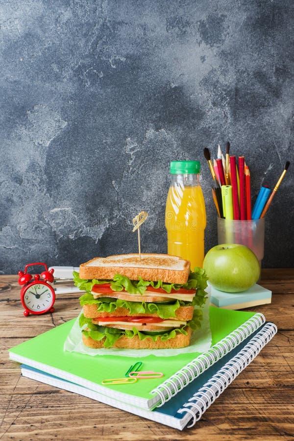 D?jeuner sain pour l'?cole avec le sandwich, la pomme fra?che et le jus d'orange Fournitures scolaires color?es assorties Copiez  photos stock